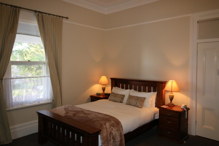 A warm looking double bed inside a room at Moore Park Inn Armidale accommodation