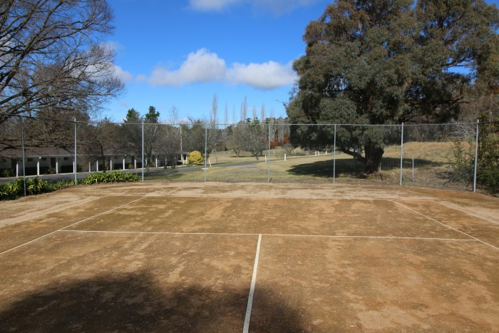 A brown tennis court close to the best accommodation in Armidale